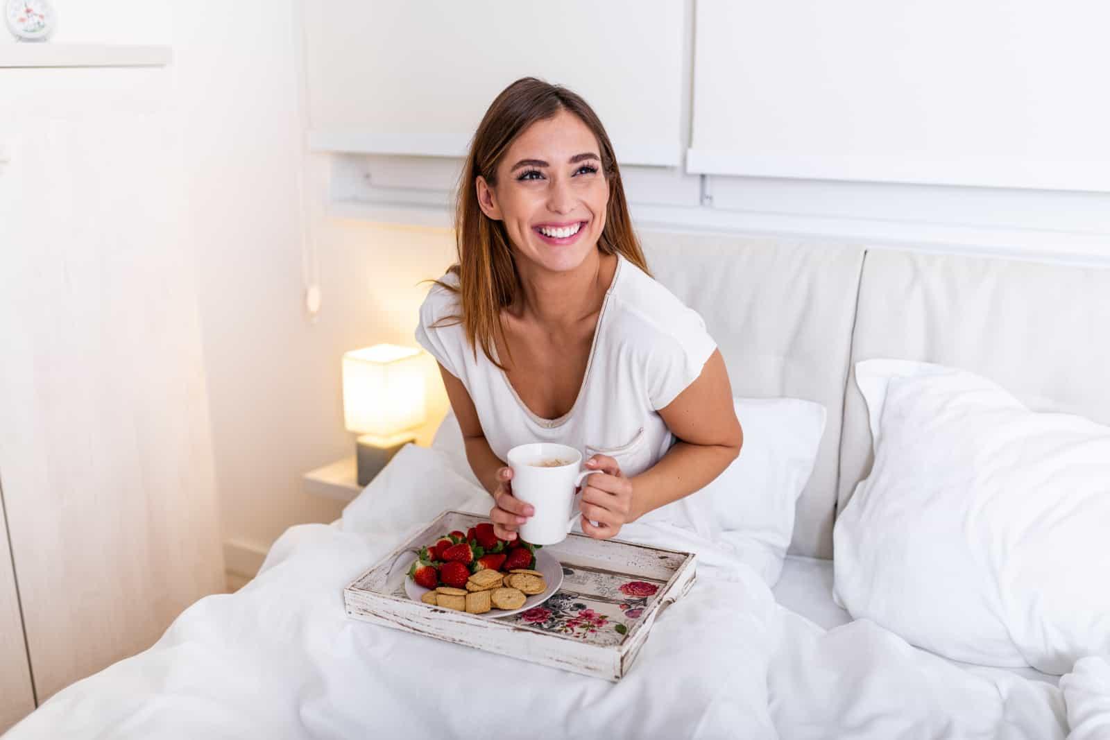 fille souriante prenant son petit déjeuner au lit