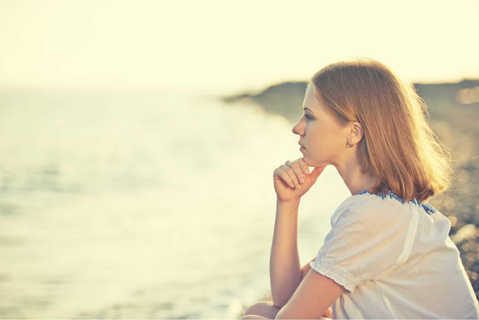 fille triste assise sur la côte sur la plage