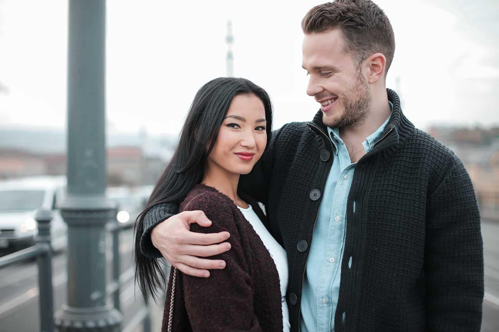 homme amoureux embrassant sa petite amie et la regardant
