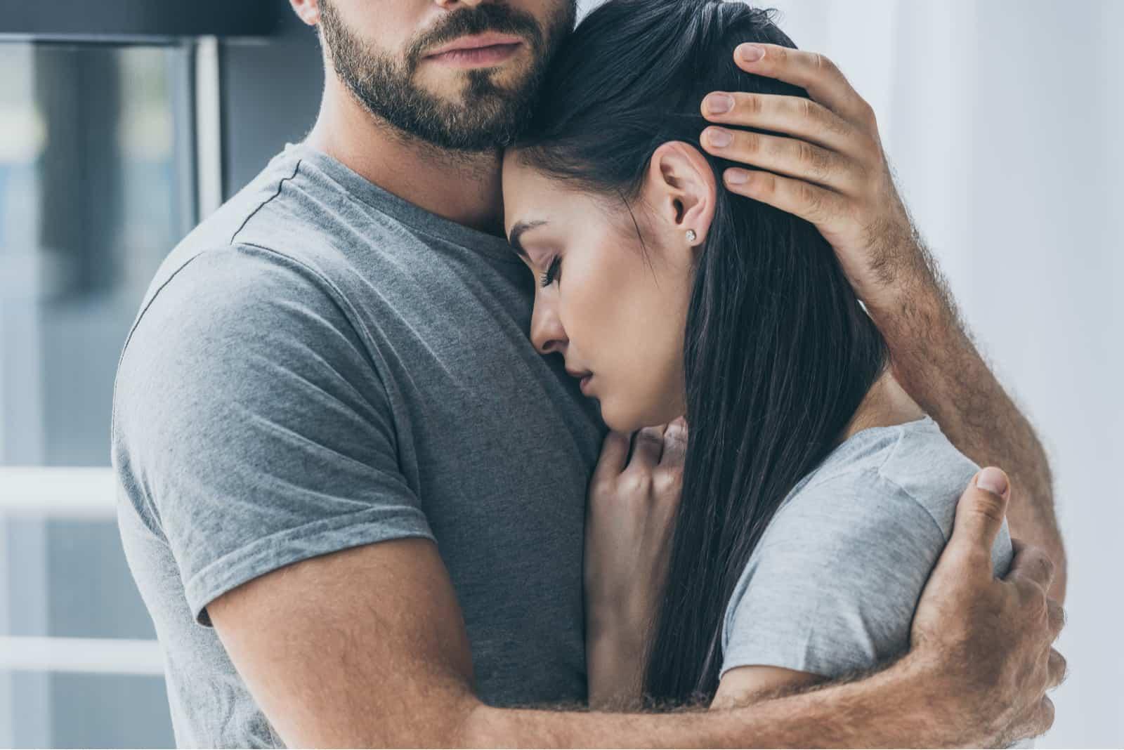 homme étreindre et soutenir jeune femme triste