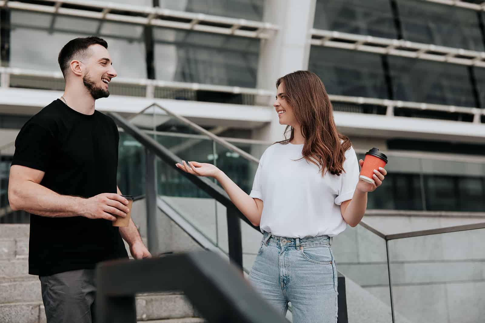 homme souriant et une femme parlant dans la rue et buvant du café