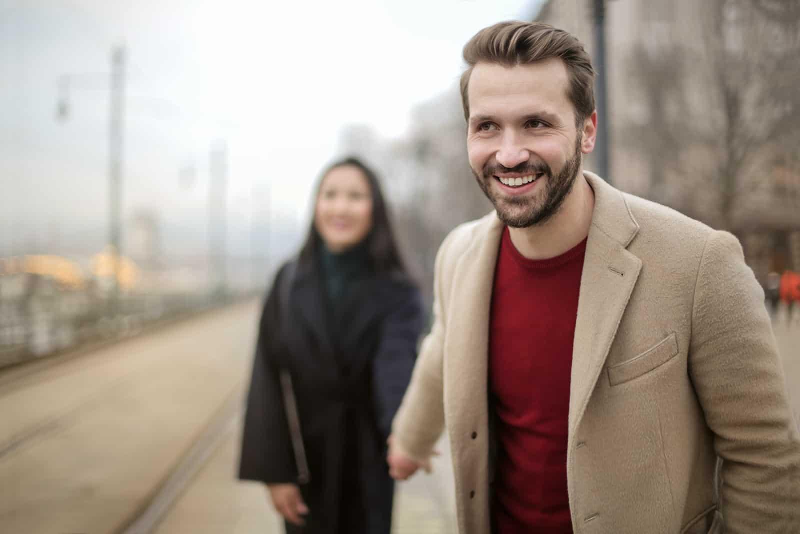 homme souriant et une femme se tenant la main en marchant sur un trottoir