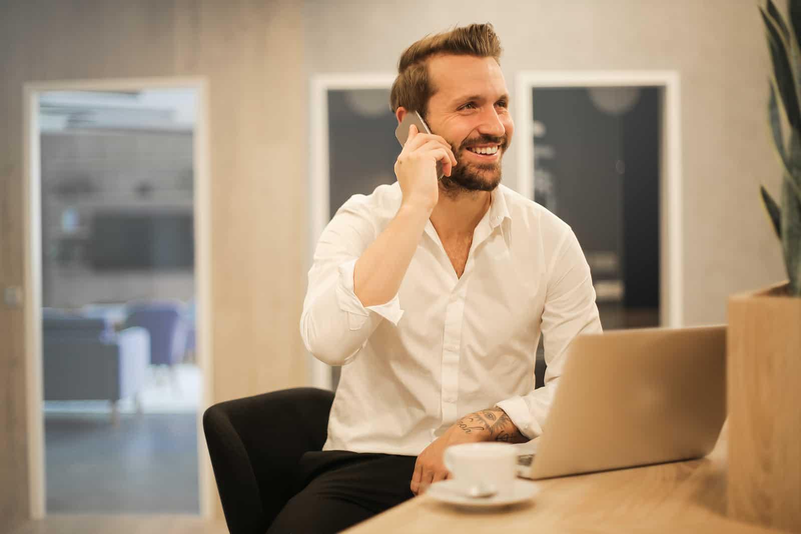 homme souriant, parler au téléphone, assis devant l'ordinateur portable