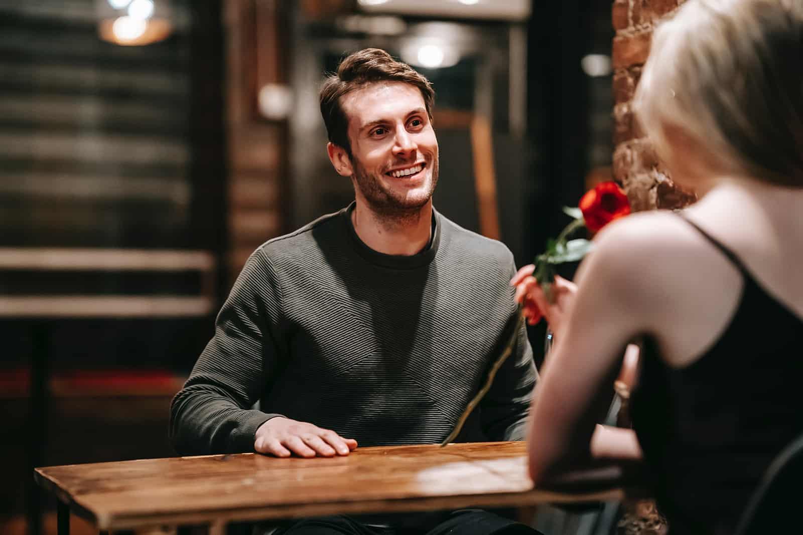 Un homme souriant regardant une femme assise avec lui et sentant la rose rouge