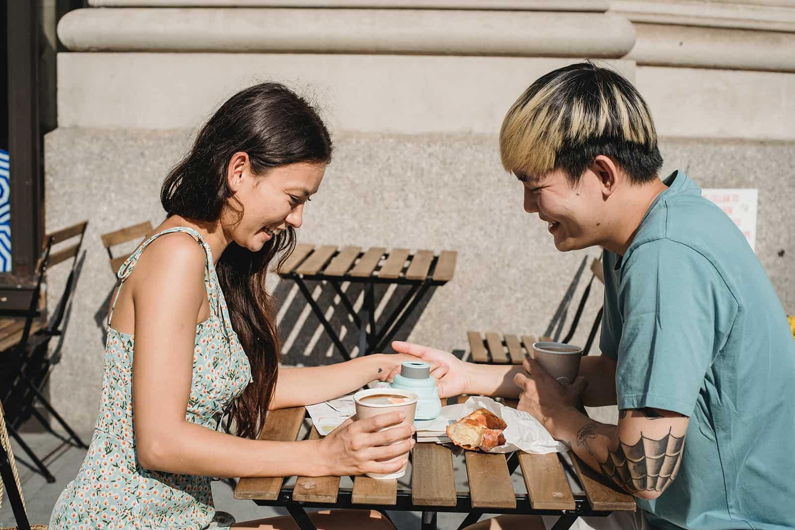 joyeux couple main dans la main assis dans le café de la rue