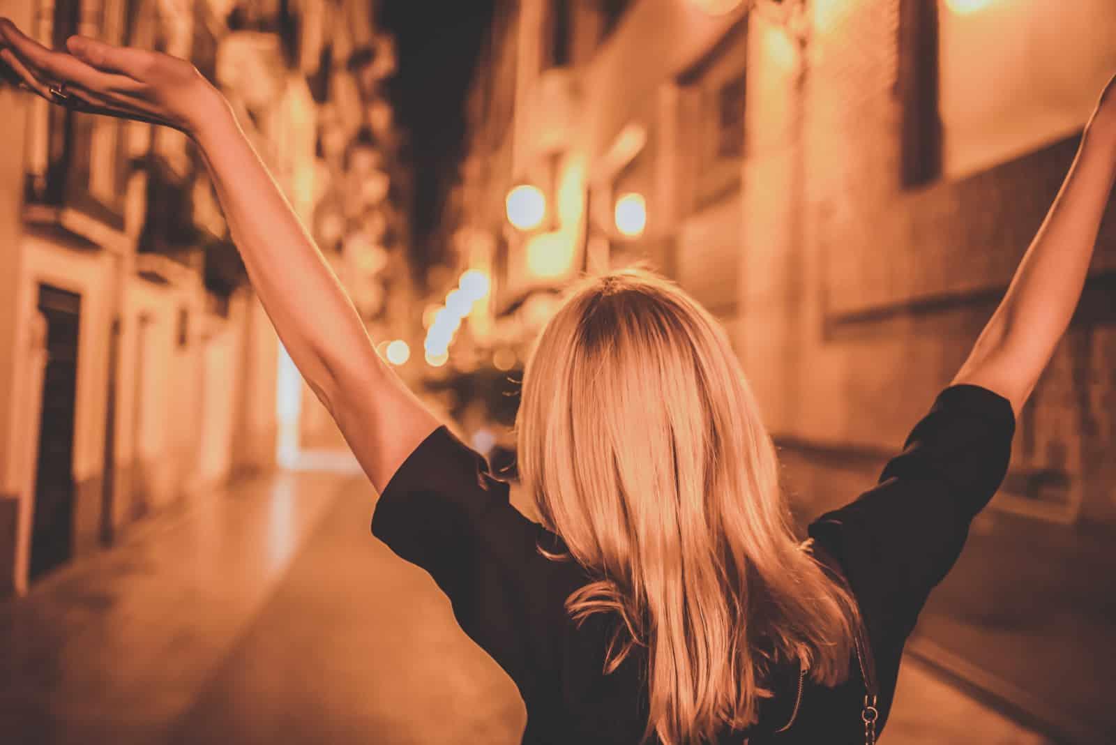 la fille marche dans les rues les bras levés en l'air