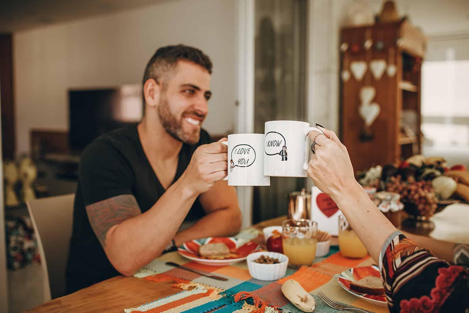 Un couple aimant tenant des tasses en céramique avec message d'amour pendant le petit déjeuner