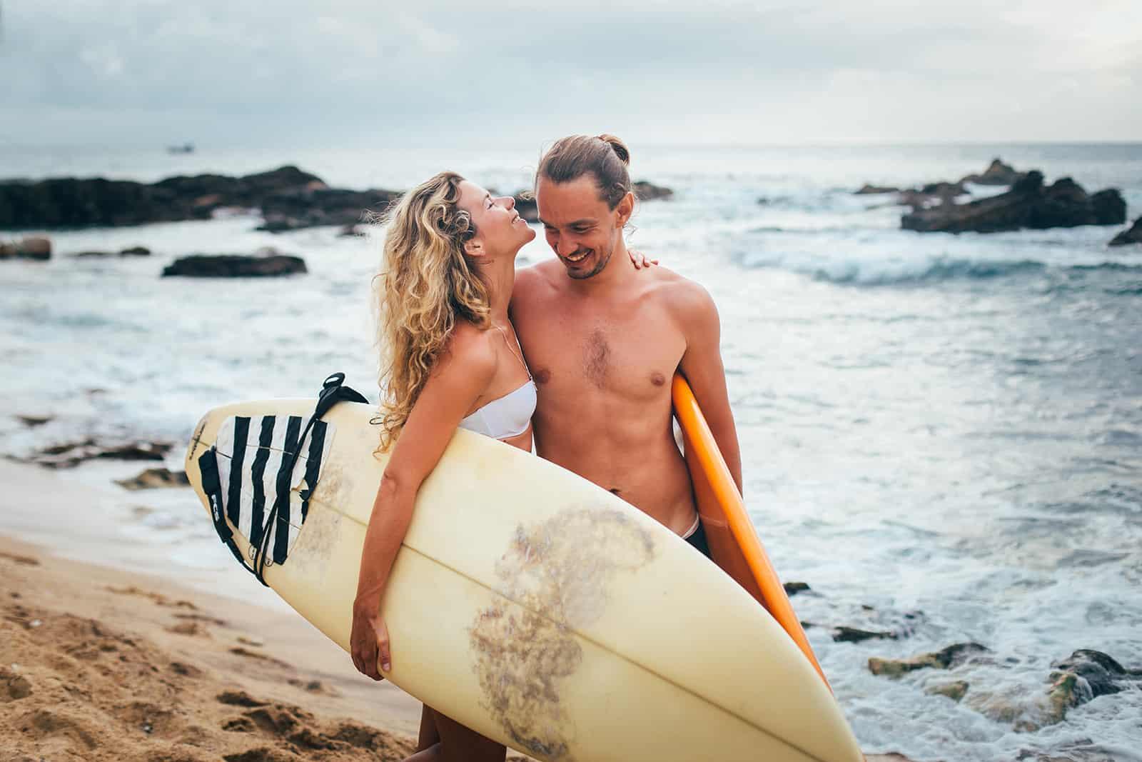 un couple amoureux étreignant tout en tenant des planches de surf sur la plage