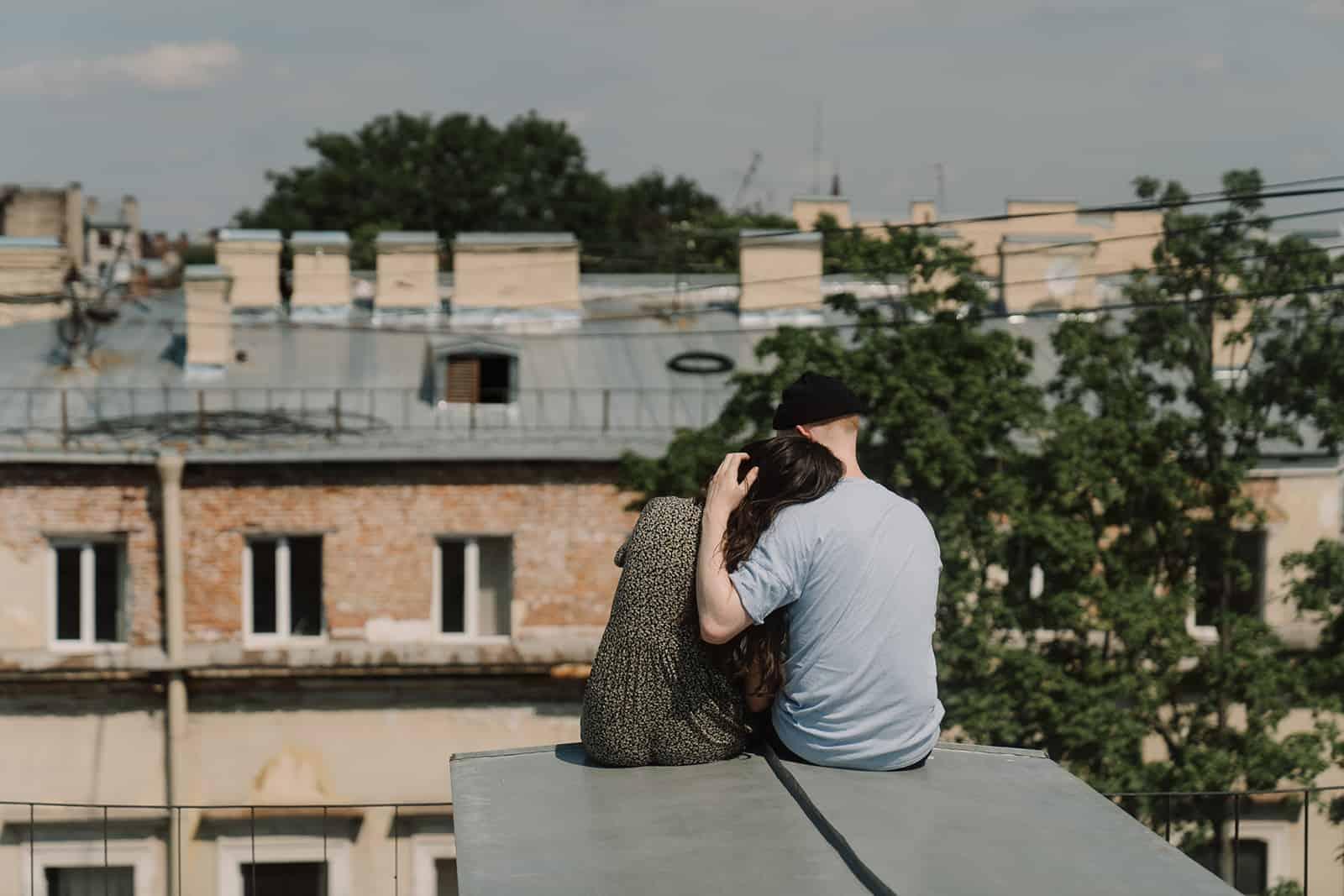 un couple assis sur le toit et se serrant dans ses bras