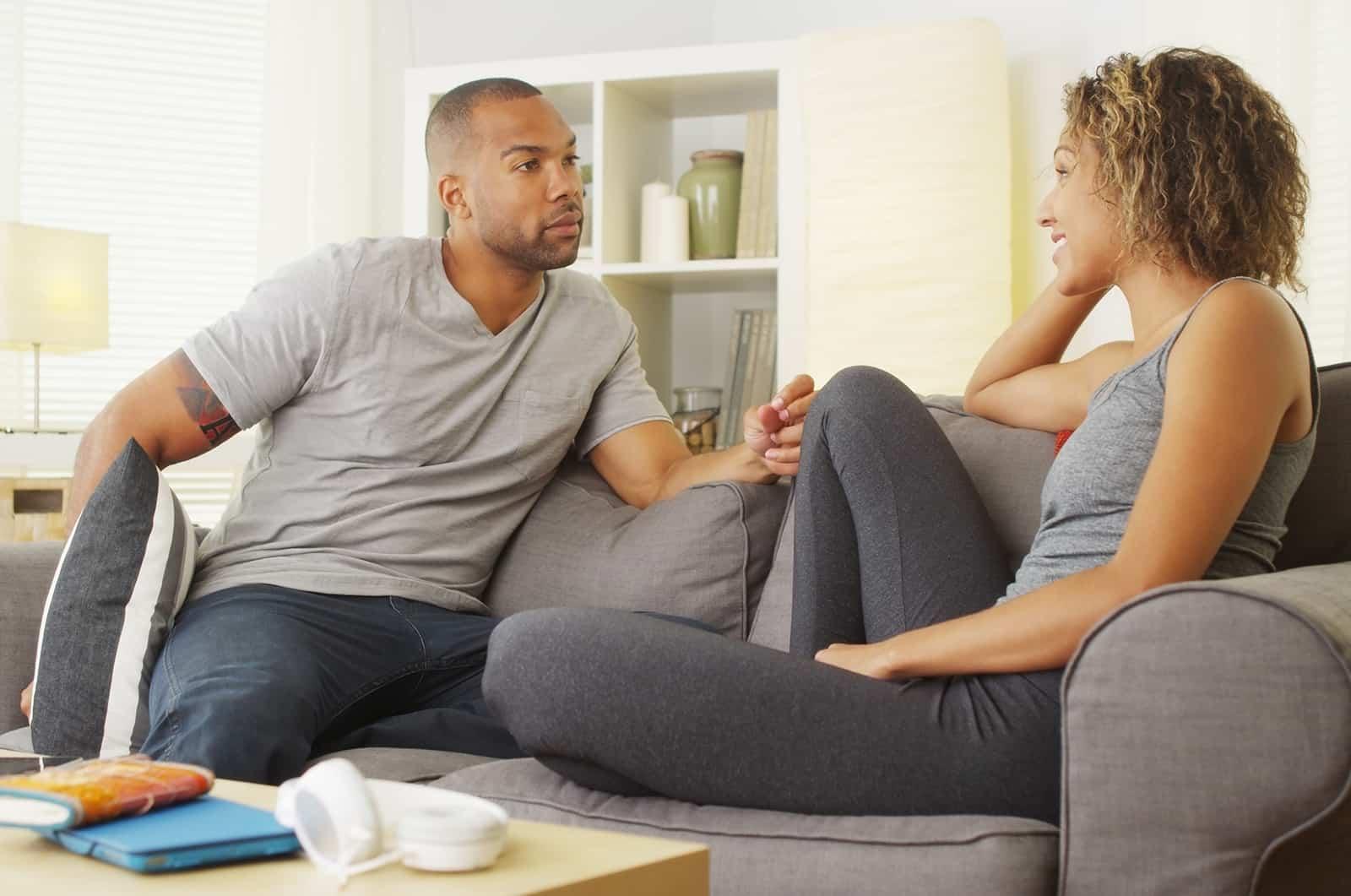 un couple ayant une conversation dans leur salon assis sur le canapé