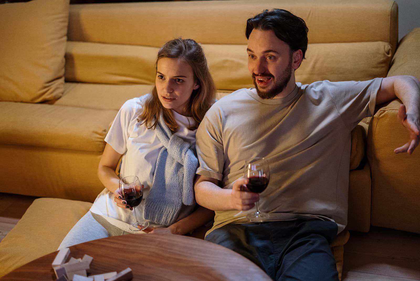 un couple buvant du vin à la maison en regardant un film ensemble