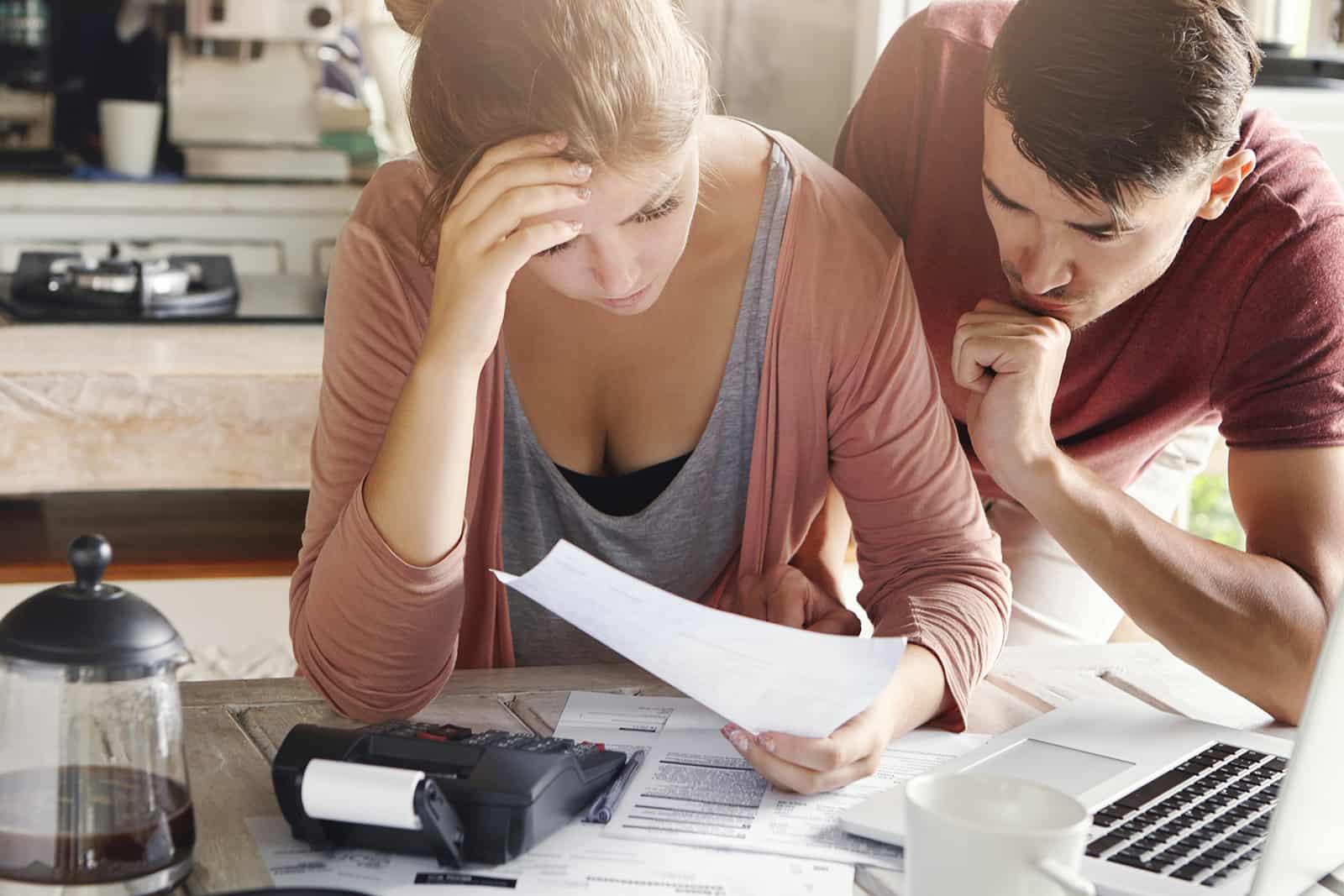 un couple calculant le budget intérieur assis dans la cuisine