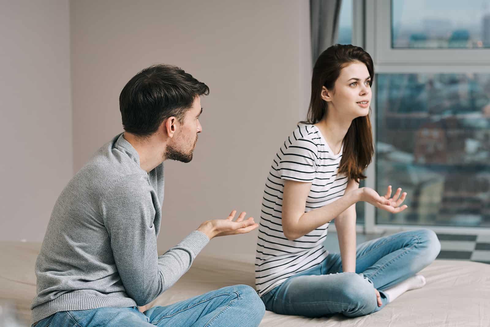 un couple discutant de leur relation assis sur le lit