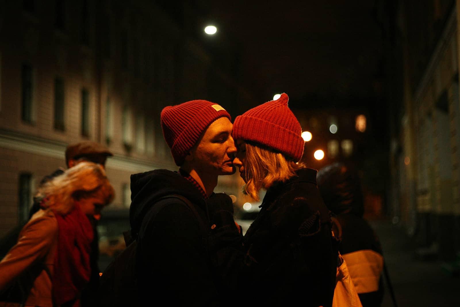 un couple étreignant la nuit dans la rue pendant que les gens marchent près d'eux