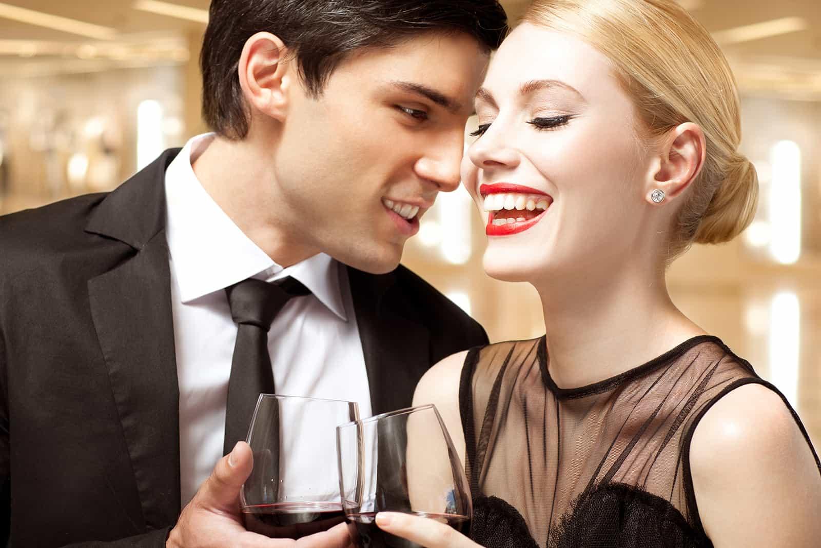 un couple gai parlant à la fête et buvant du vin