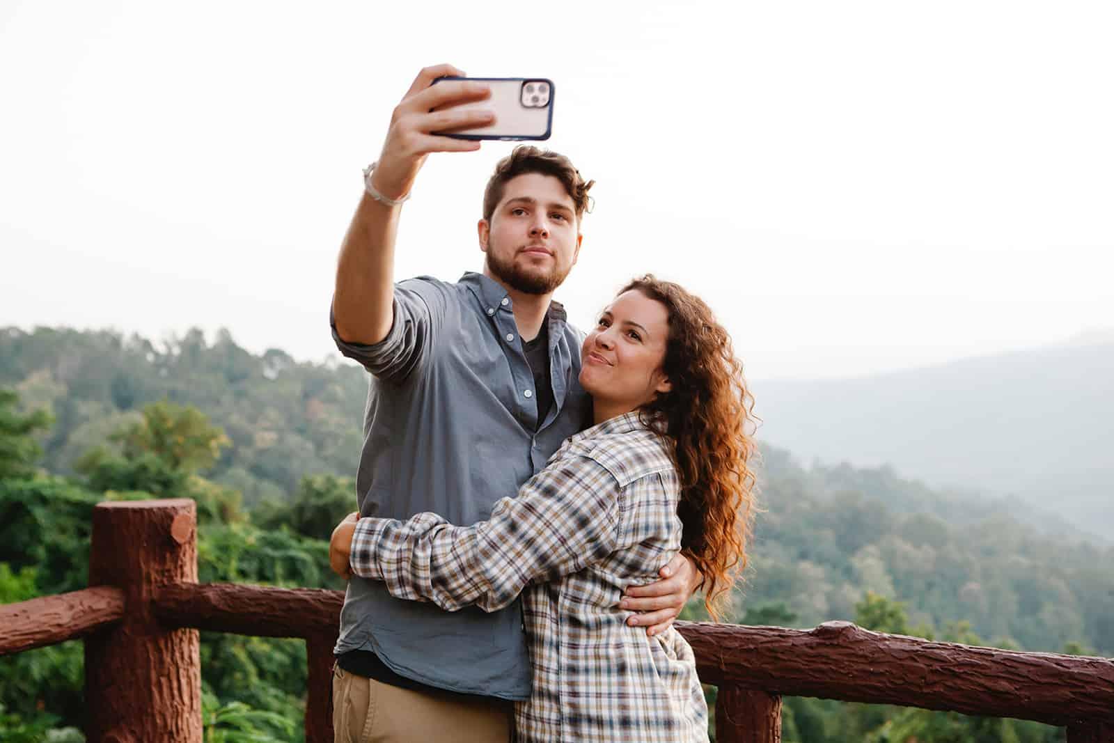 un couple prenant un selfie avec smartphone en se tenant debout sur la terrasse