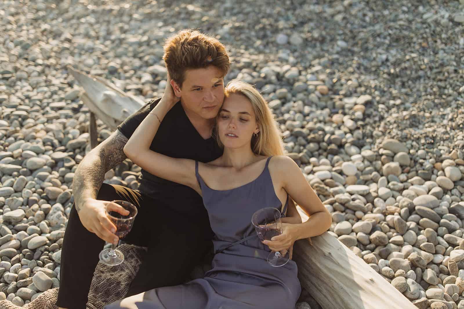 un couple romantique assis sur la plage de galets et boire du vin