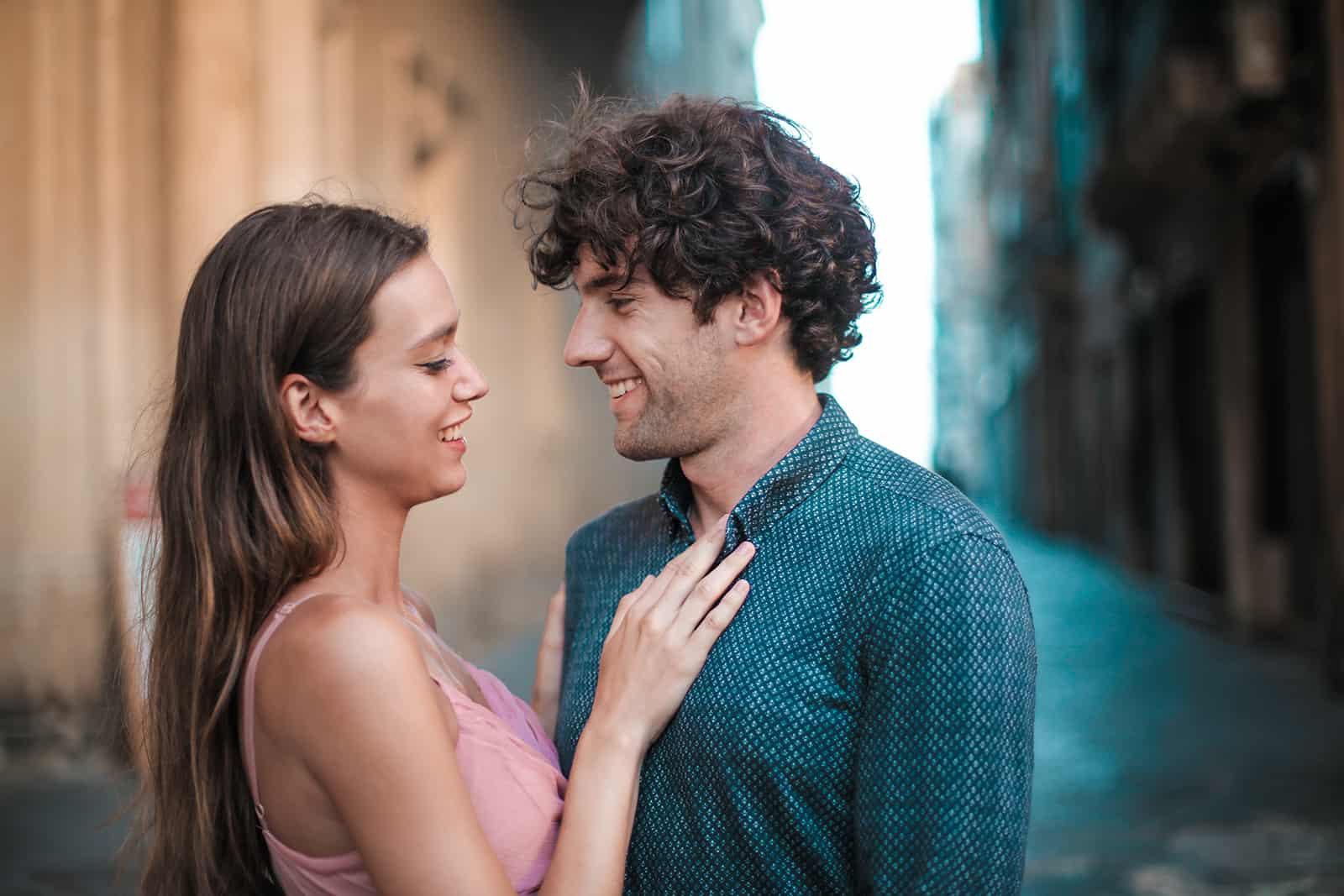 un couple souriant face à face debout dans la rue