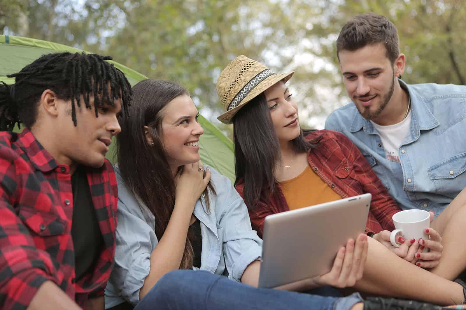 un groupe d'amis assis dans la nature et utilisant une tablette