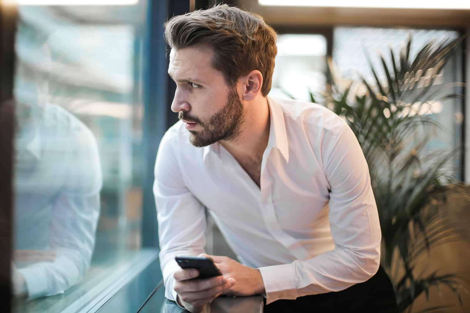 un homme confus regardant par la fenêtre et tenant le smartphone