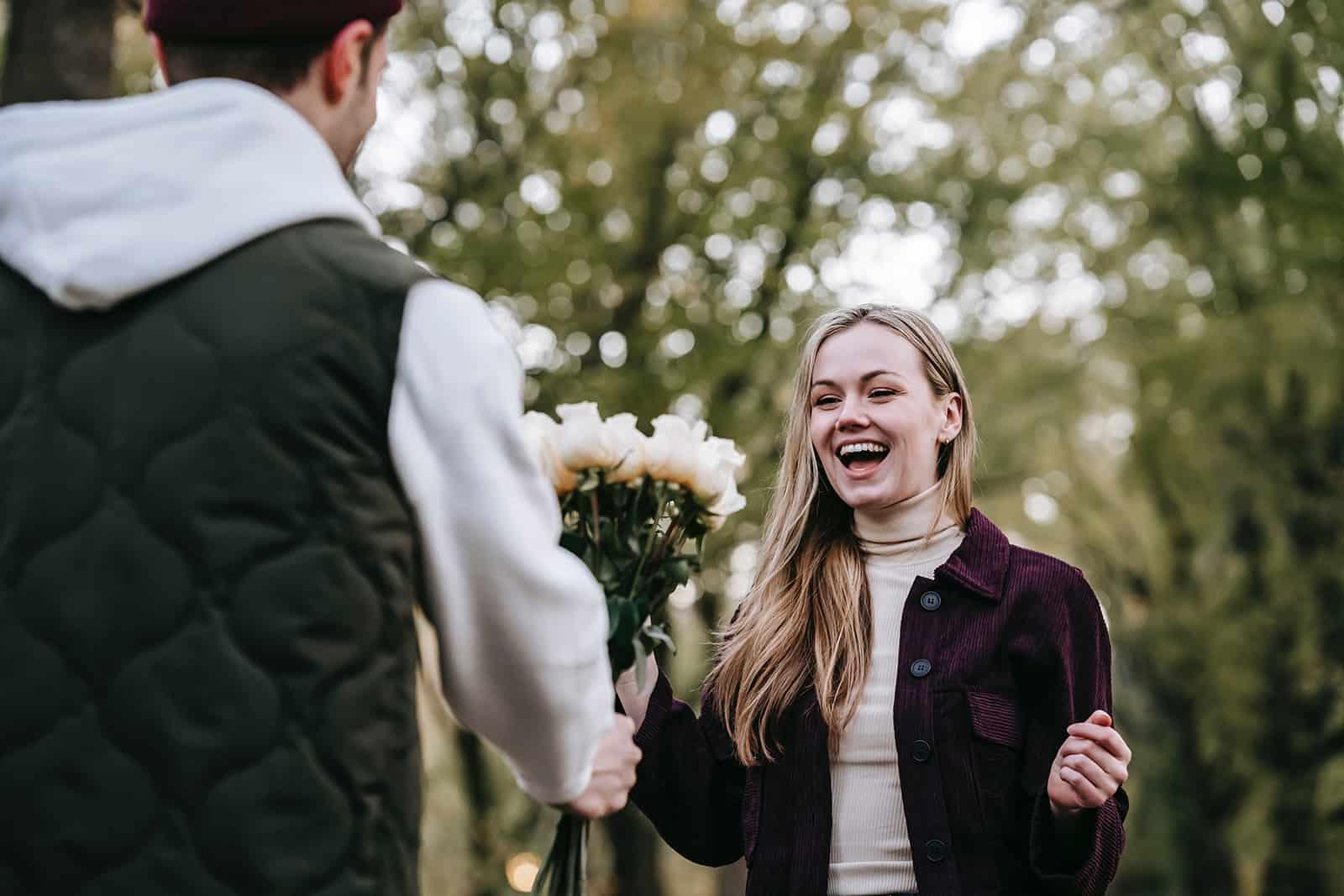 un homme donnant des fleurs à une femme souriante à une date