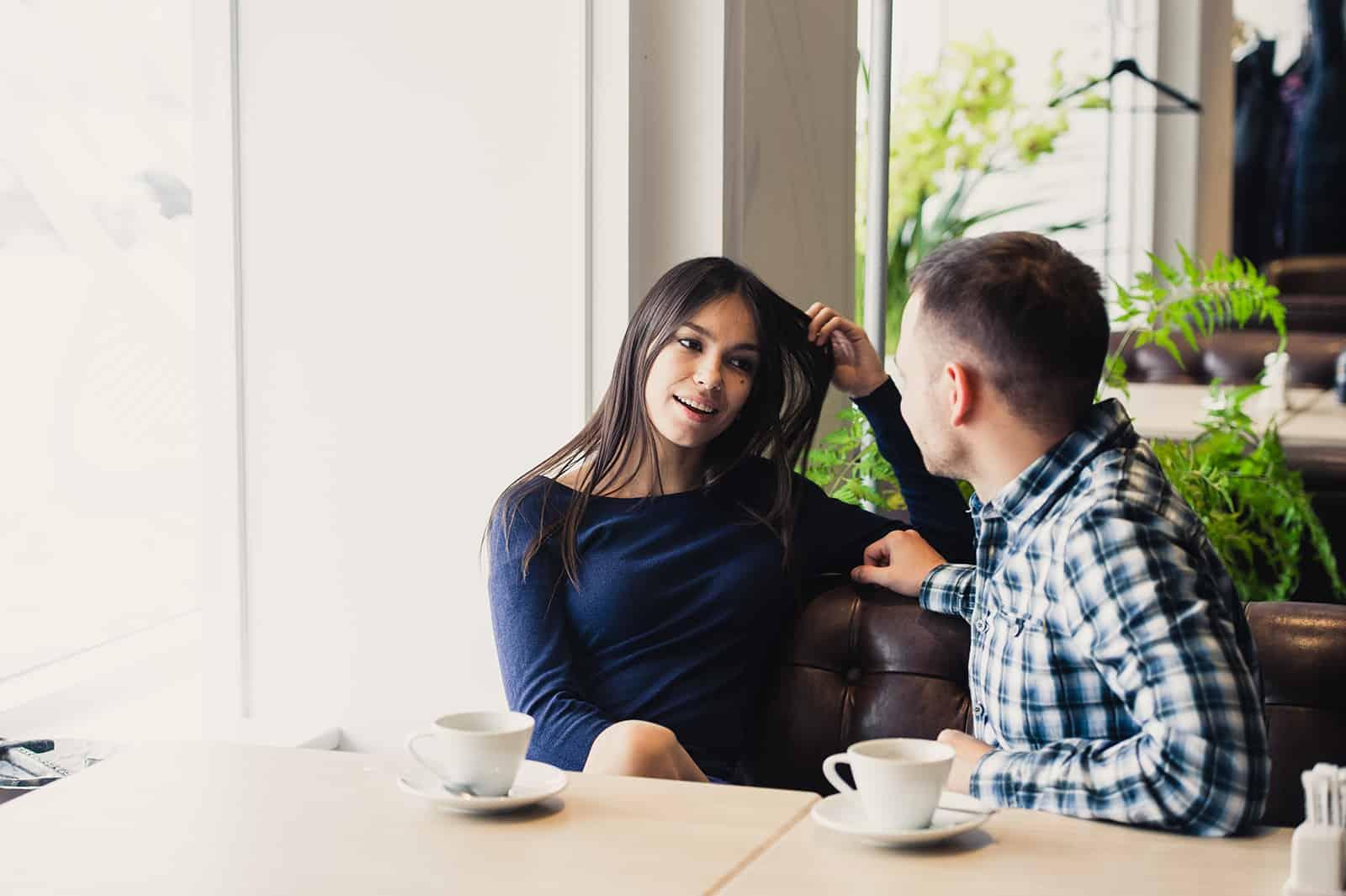 un homme et une femme assis dans le café à parler et flirter