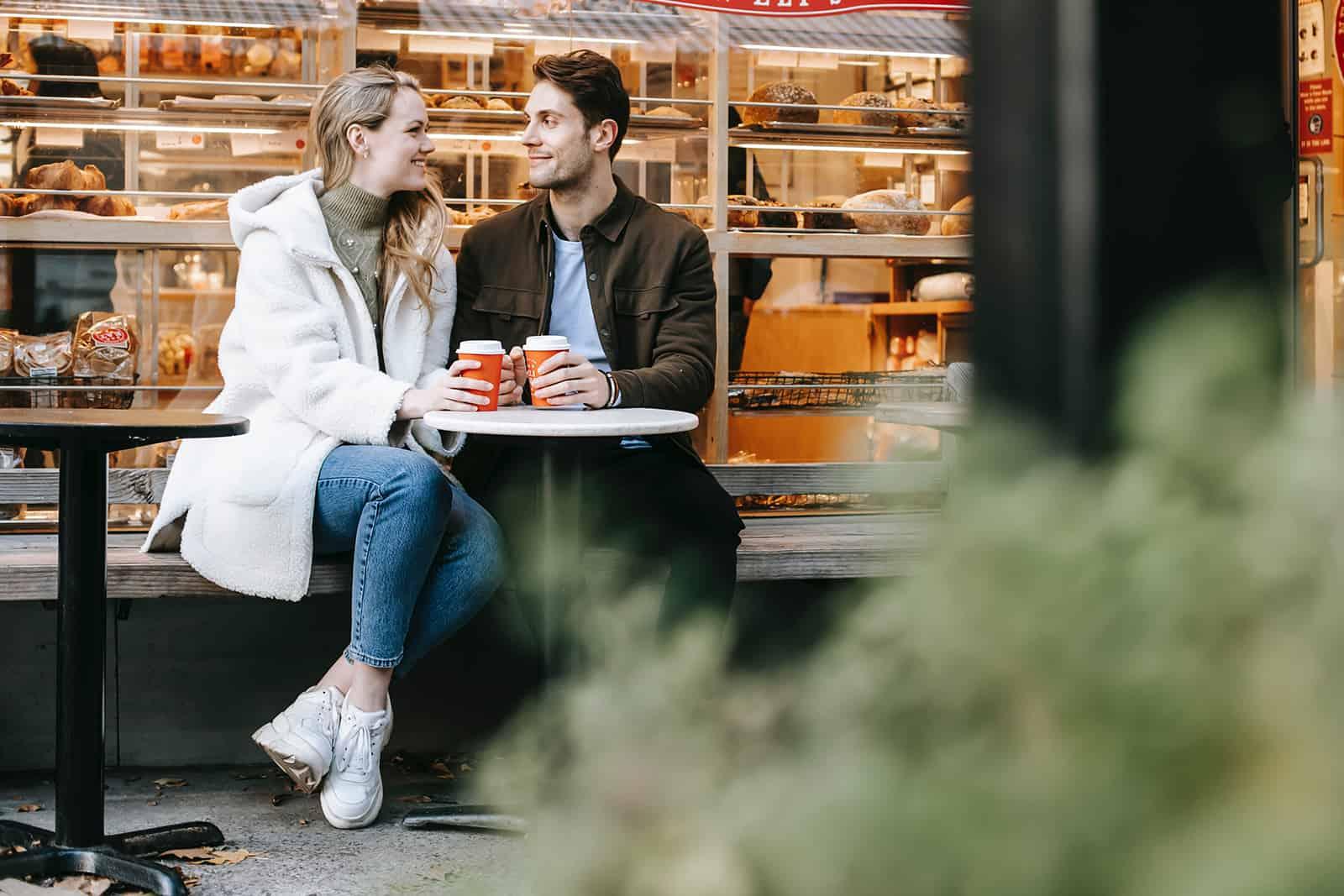 un homme et une femme assis dans un café de rue et se regardant