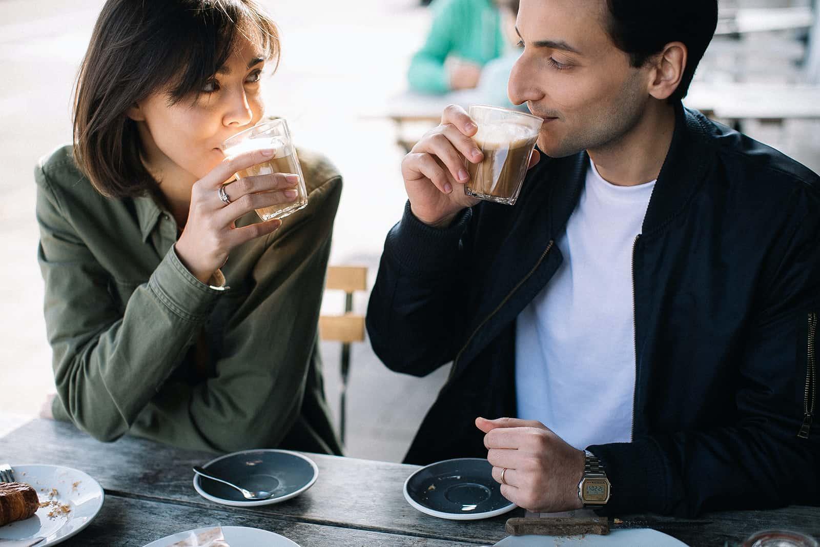 un homme et une femme buvant du café et se regardant à une date