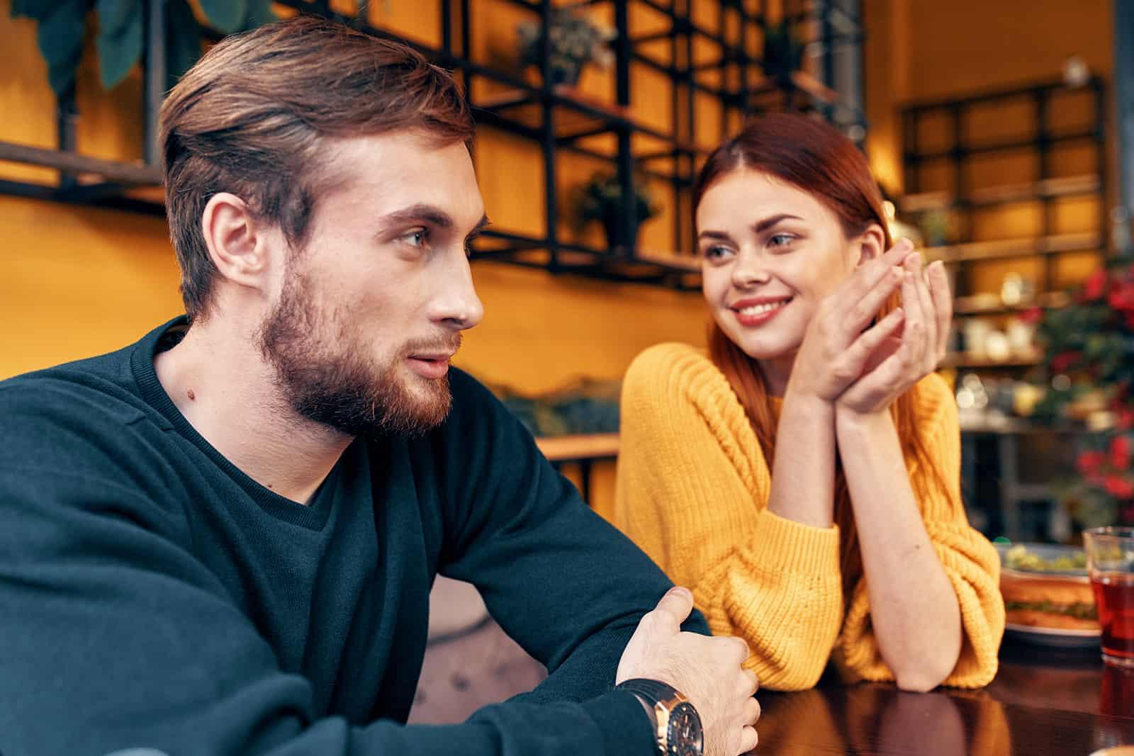 un homme et une femme joyeux qui parlent dans le café