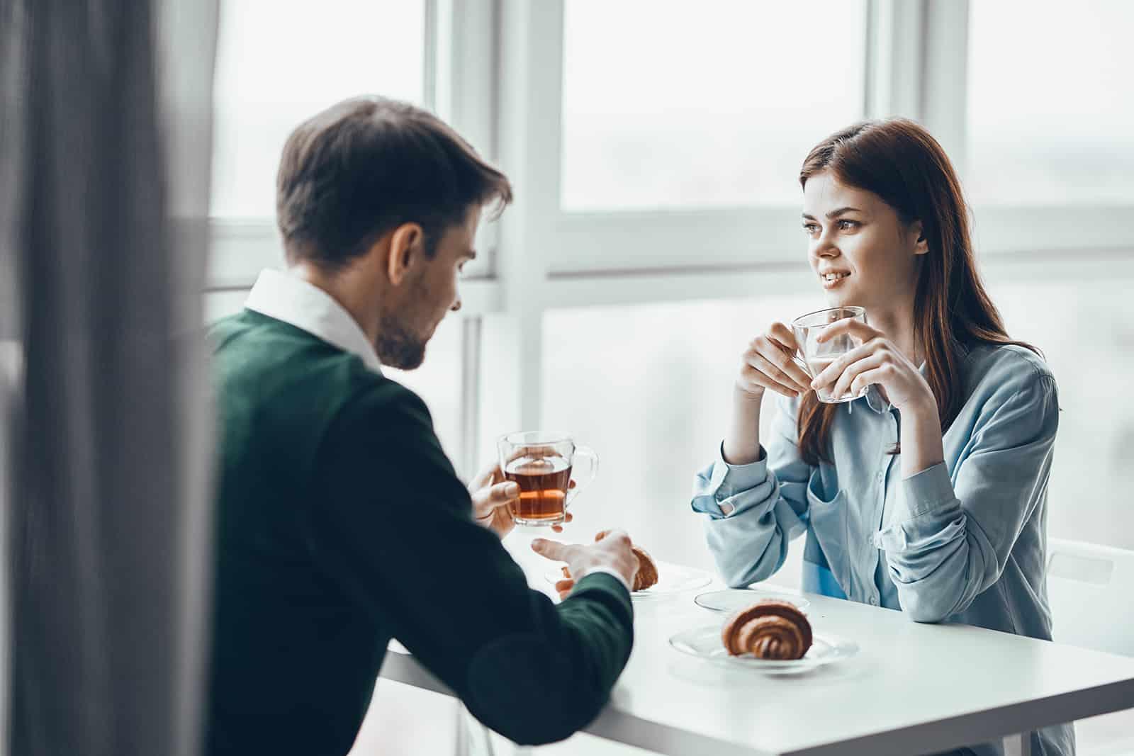 un homme et une femme prenant le petit déjeuner ensemble et parlant