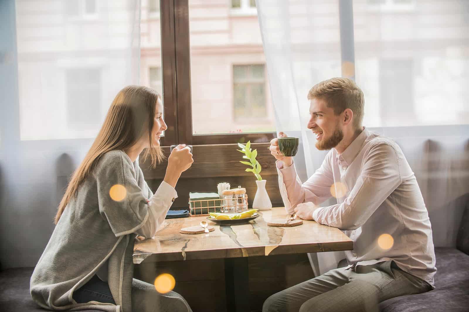 un homme et une femme parlant dans le café à une date