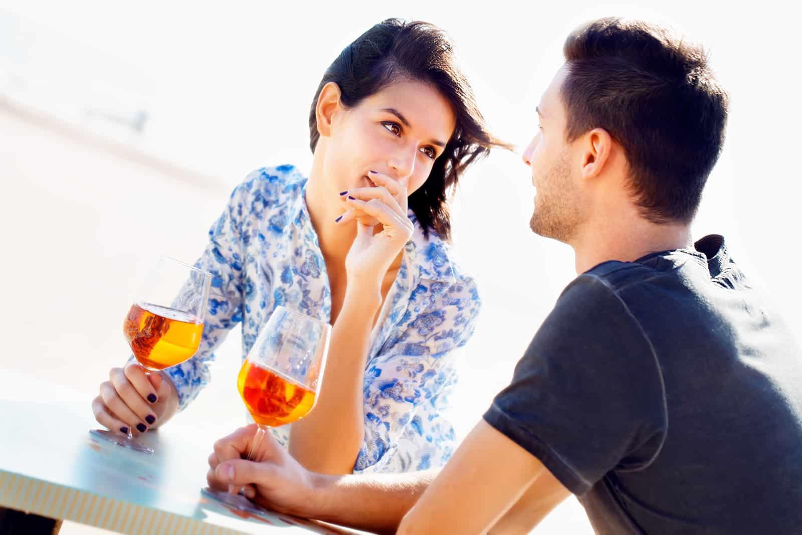un homme et une femme se regardant dans les yeux tout en buvant du vin ensemble