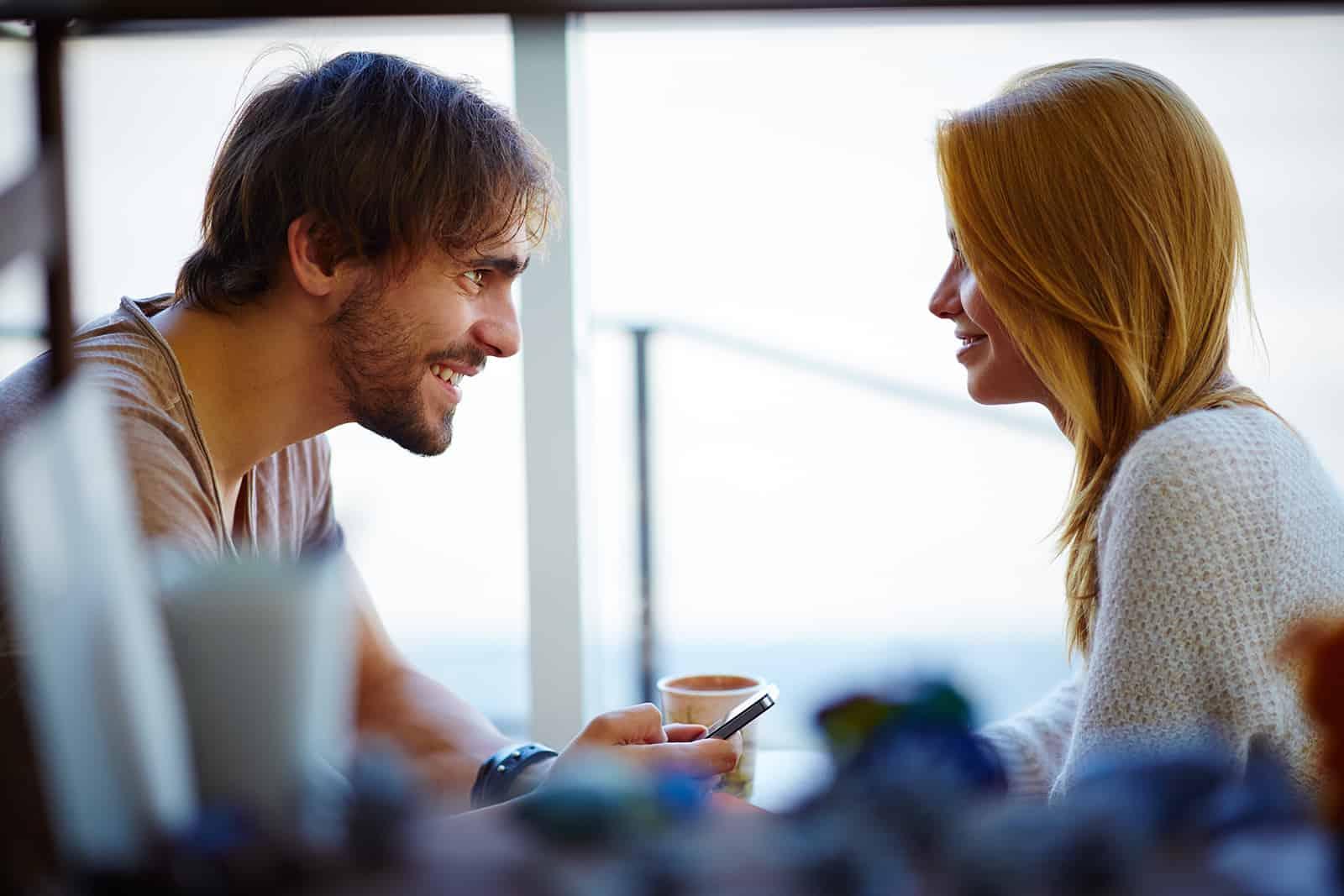 un homme et une femme se regardent et parlent dans le café