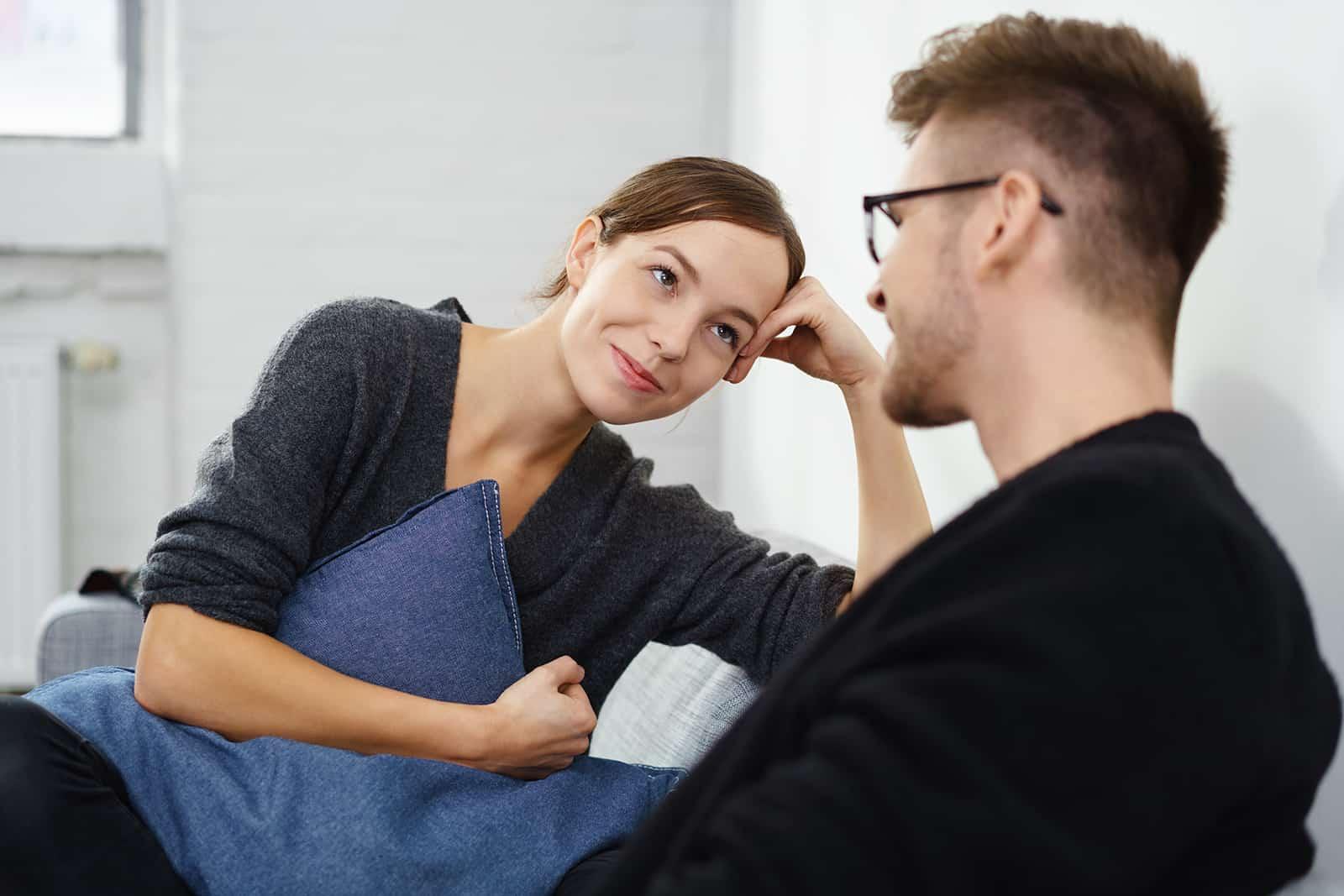 un homme et une femme souriants et se regardant dans les yeux assis sur le canapé