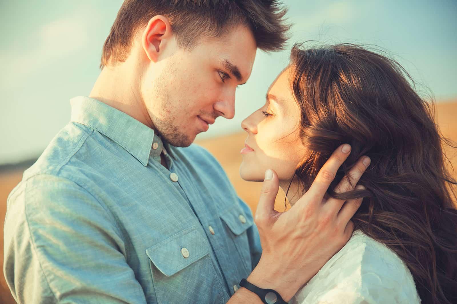 un homme et une femme souriant et se regardant sur le point de s'embrasser