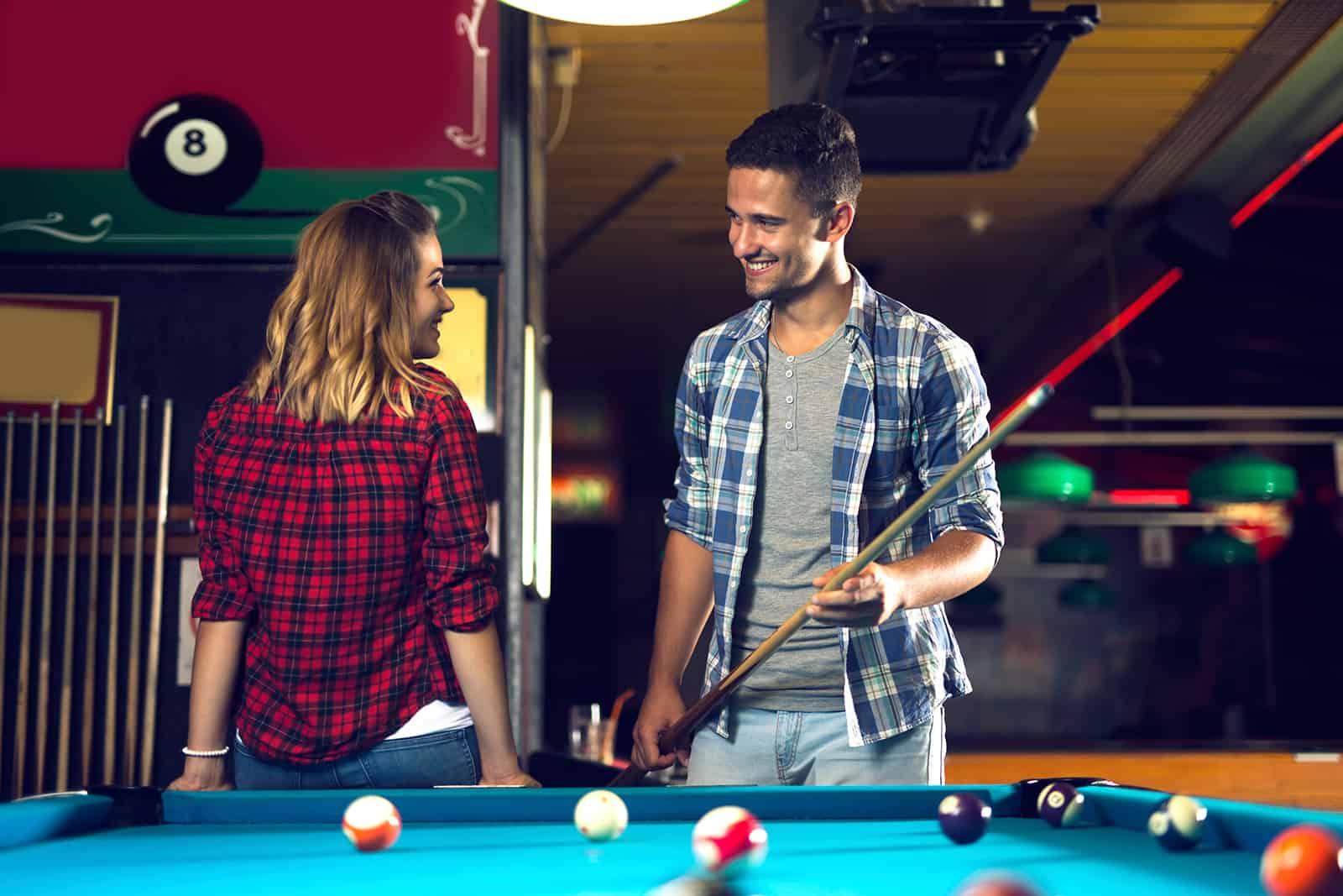 un homme flirter avec une femme et jouer au billard dans la salle de billard