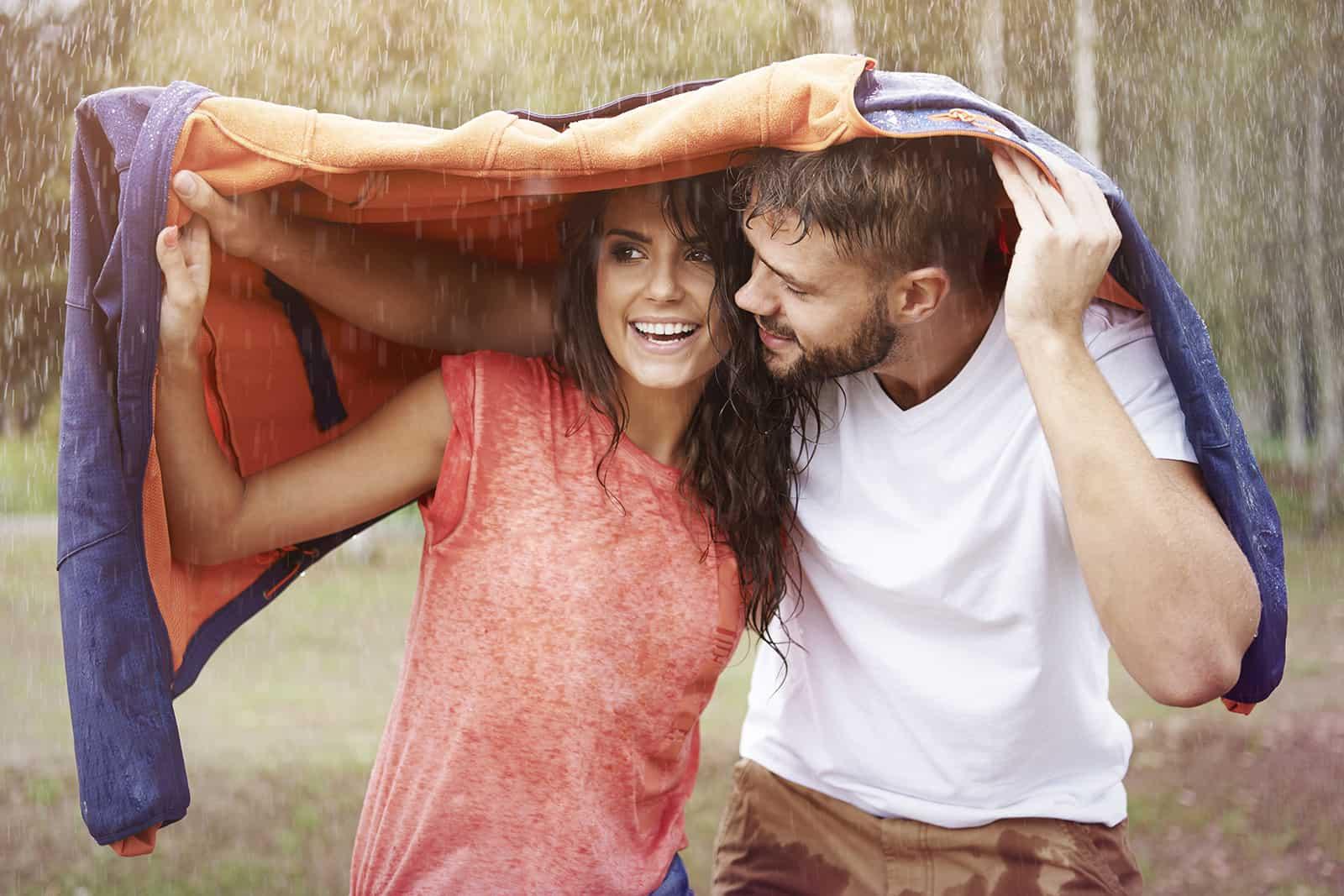 un homme protégeant une femme de la pluie avec sa veste et la regardant