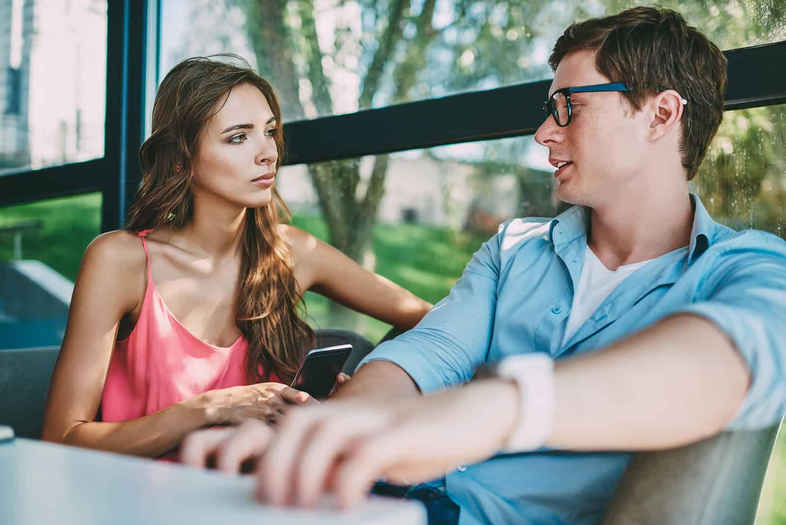 Un homme regardant une femme sérieuse assise à côté de lui et tenant un smartphone