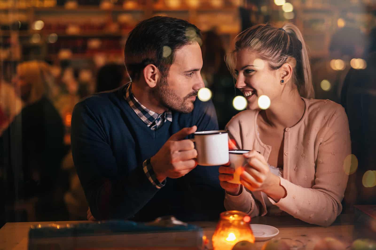 Un homme à la recherche d'une femme souriante dans les yeux tout en buvant du thé ensemble dans le café