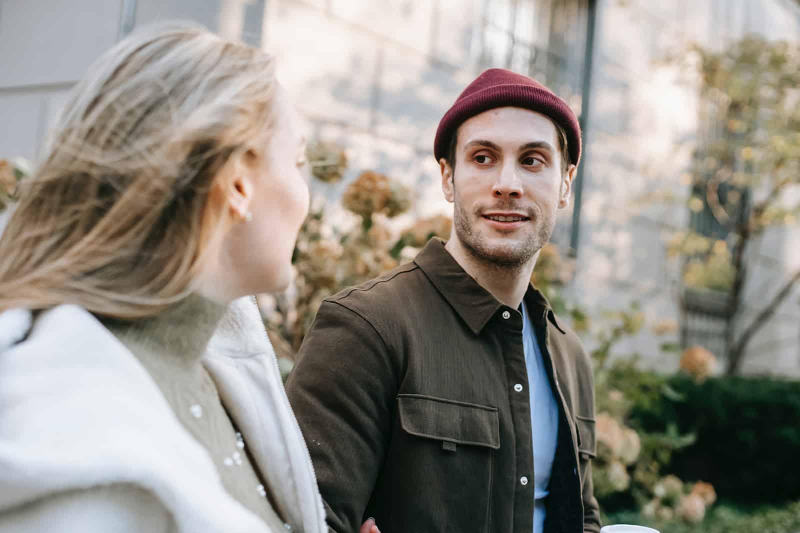 un homme regardant une femme marchant avec lui dans la rue