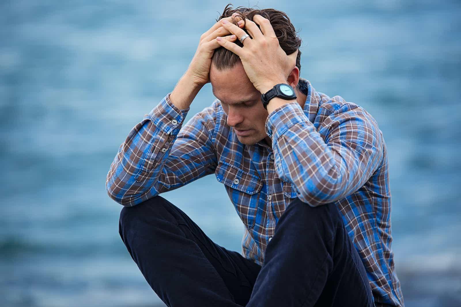 Un homme se sentant blâmé assis seul sur le rocher tenant la tête avec les mains