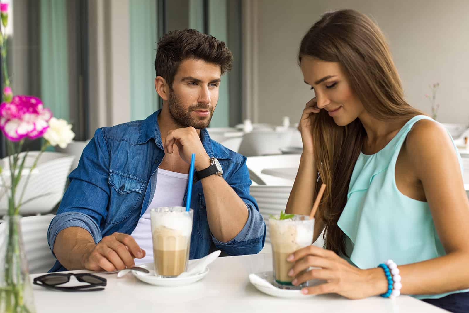 Un homme séduisant flirter avec une femme assis dans le café ensemble