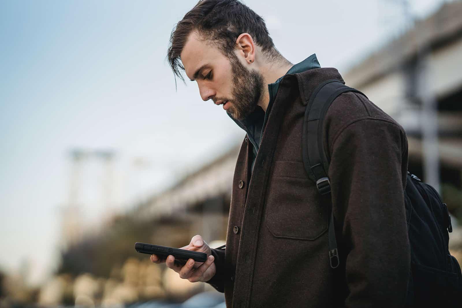 un homme sérieux bavardant sur son smartphone en se tenant debout dans la ville