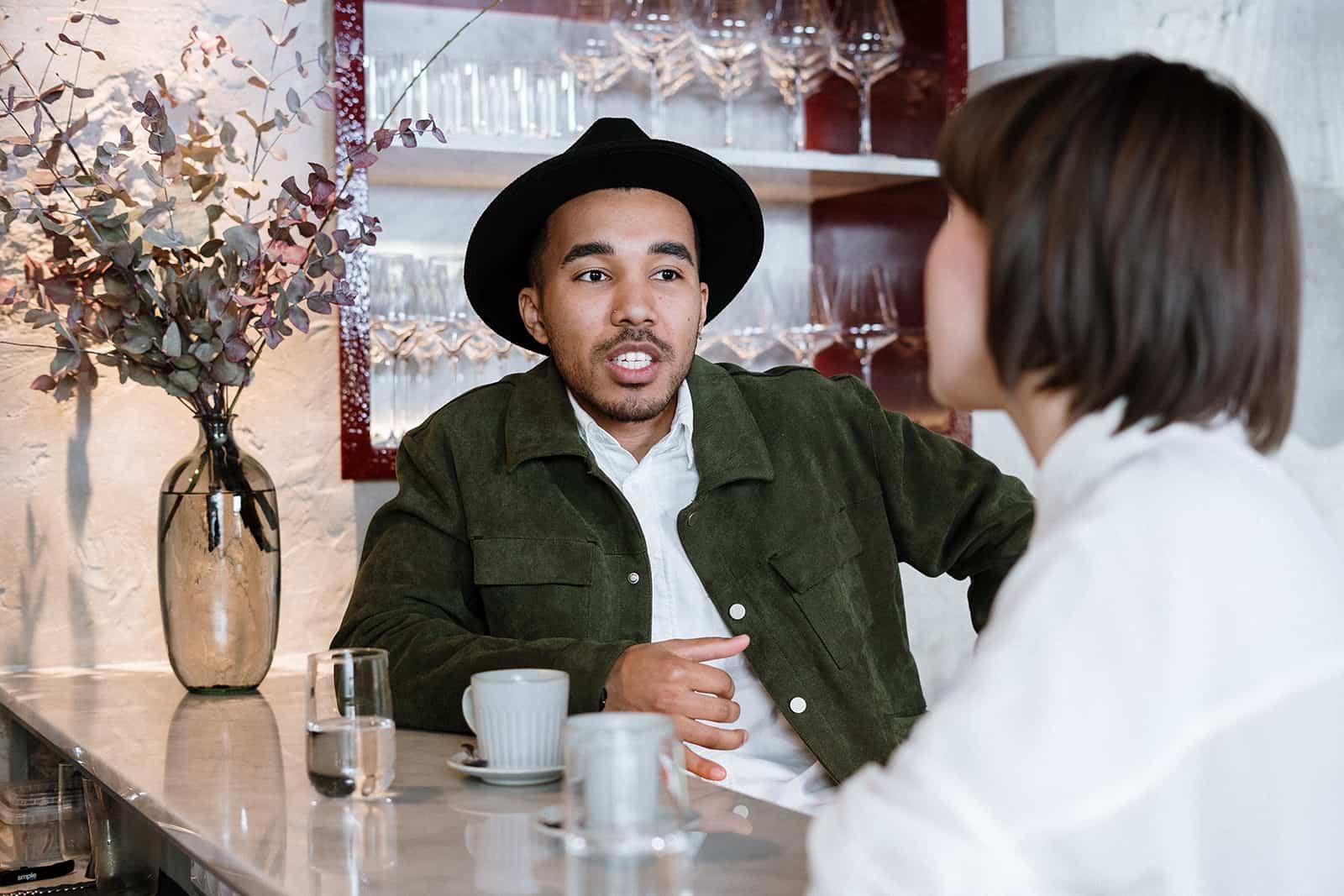 Un homme sérieux parlant avec une femme assis ensemble dans un café