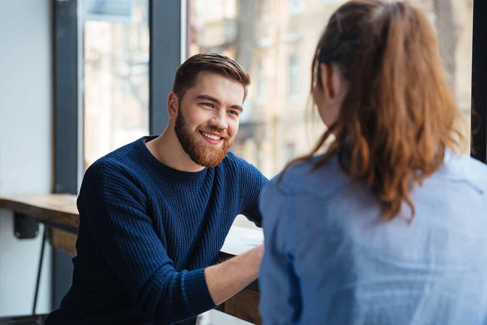 Un homme souriant écoute attentivement une femme assise avec lui dans un café près de la fenêtre