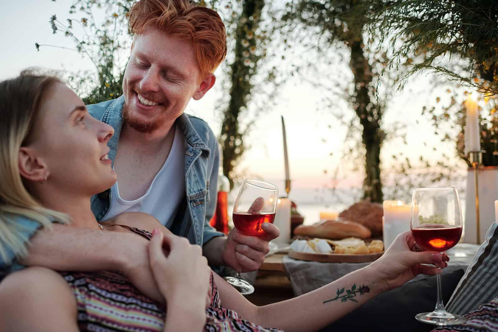 Un homme souriant embrassant sa petite amie lors d'un dîner romantique en plein air
