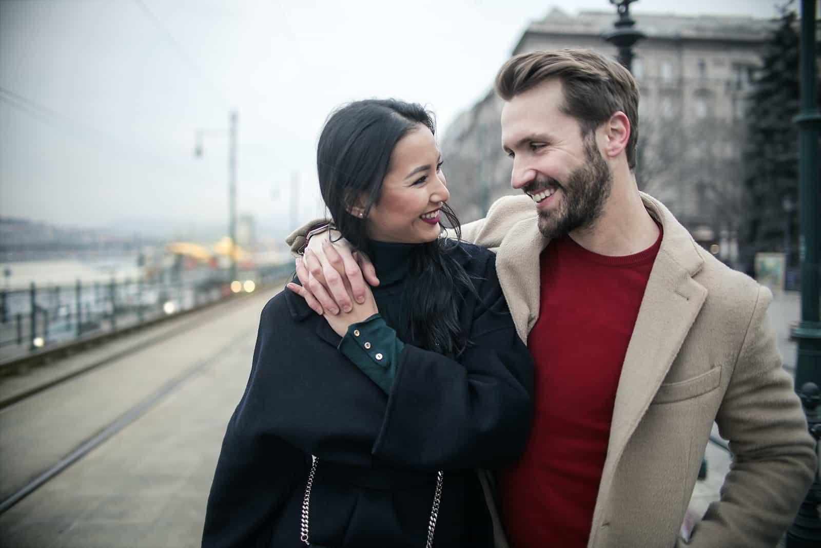 un homme souriant embrassant une femme souriante en marchant ensemble