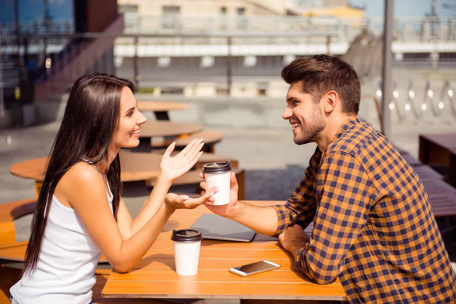 un homme souriant et une femme parlant dans le café et s'amusant
