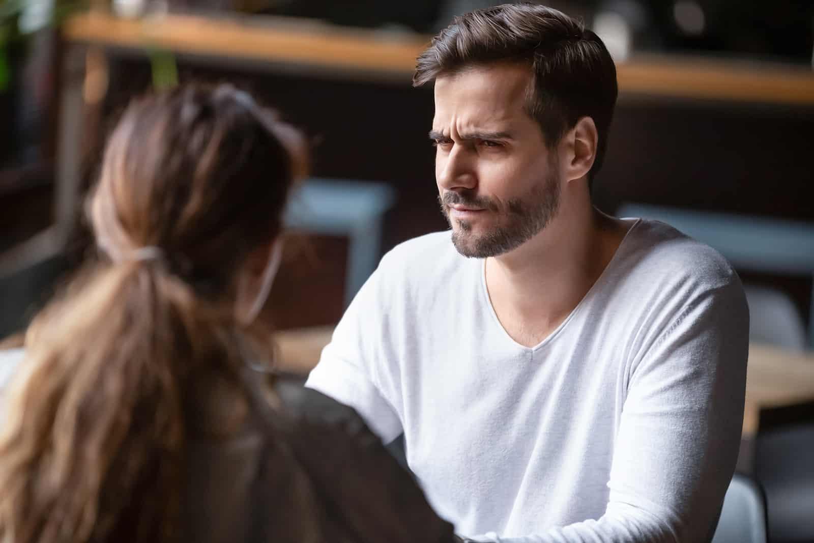 Un homme surpris regardant une femme alors qu'il était assis dans le café ensemble