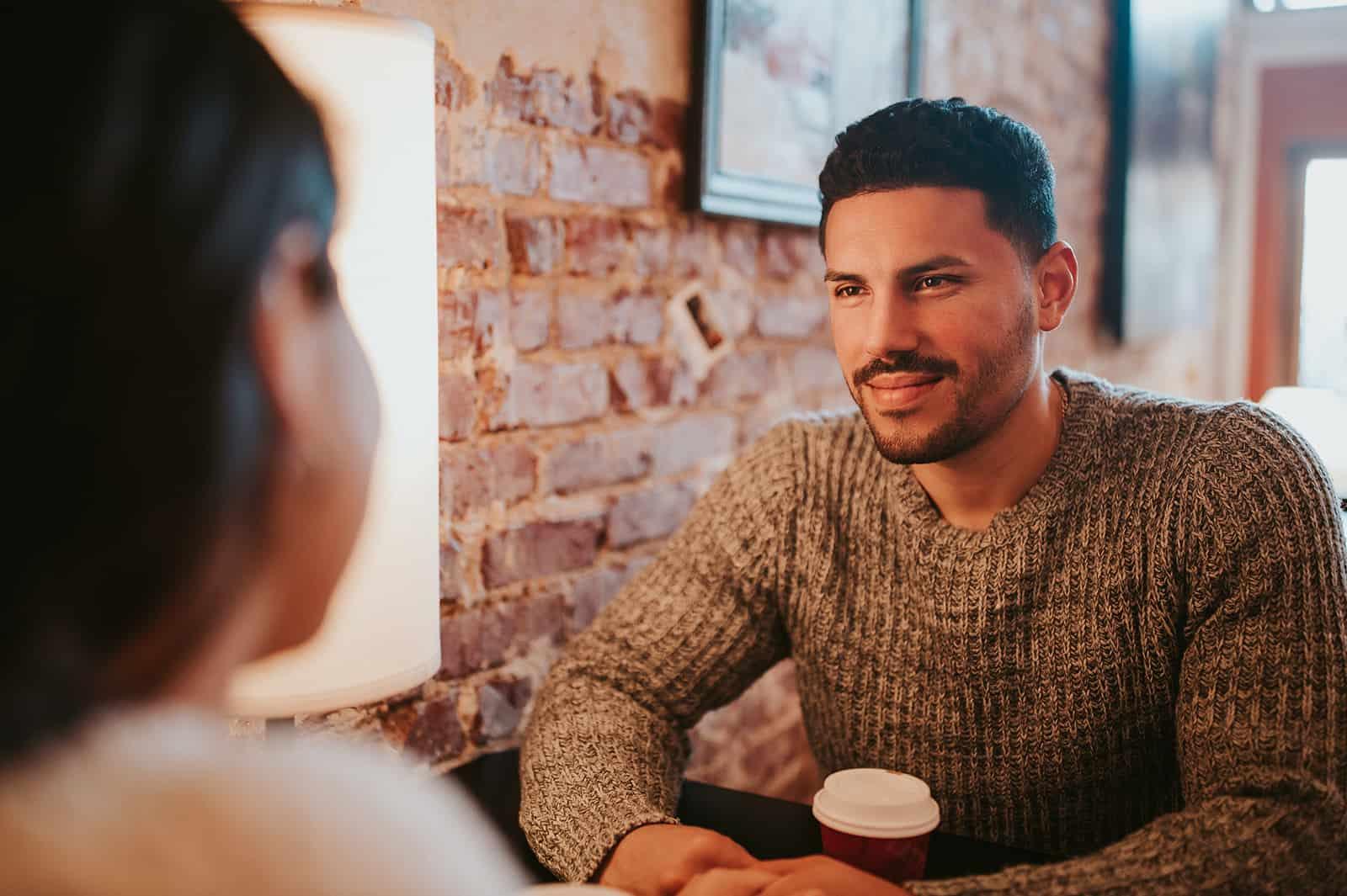 un homme tenant la main avec une femme à travers la table dans le café